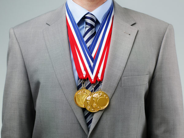 Gold medals hanging around a businessman neck concept for success and winning in business